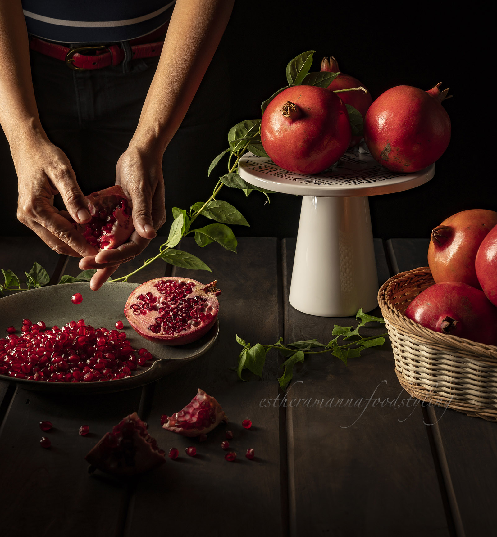 Fresh produce with pomegranates being shelled with hands. Food styling with a moody effect.